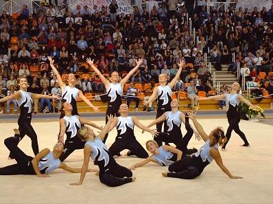 11 Turnerinnen in schwarz-weißen Anzügen beim Ende der Kür