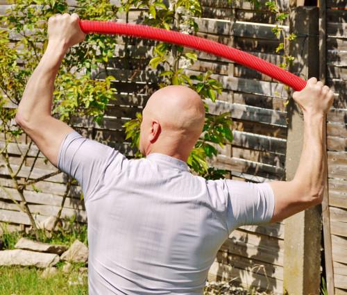 Mann hält roten Trainingsstab mit beiden Händen über dem Kopf