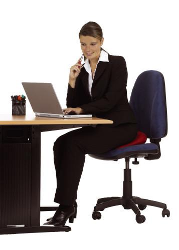 Frau im schwarzen Kostüm sitzt am Schreibtisch vor aufgeklapptem Laptop